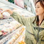 A young woman grocery shopping in the prepared foods section, reading nutrition facts and wearing a warm coat.