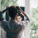 a brunette young woman looks pensive as she looks at her reflection in the mirror.