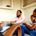 a family is engaging in a group therapy session; father is smiling, full of hope. Men and depression are commonly misunderstood.