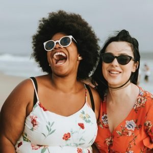 Two women laughing at the beach.