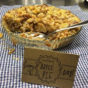 "Homemade apple pie with a handwritten sign that says ""Happy National Apple Pie Day!"""
