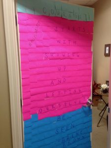 "Amy's office door covered in sticky notes that says ""Courage starts with showing up and letting ourselves be seen"" by Brene Brown"
