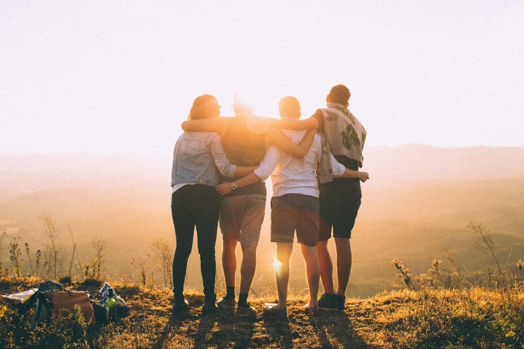 Four young adults with backs facing the camera on top of a hill looking at the sunset