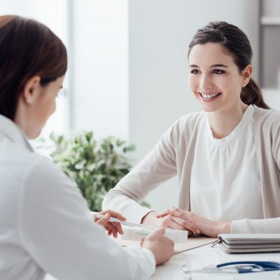 Female patient meeting with clinician, smiling