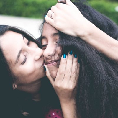 A happy mother, kissing her daughter.