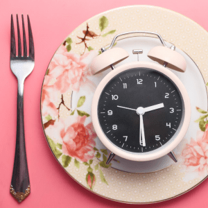 an alarm clock on an ornate, pink plate, symbolizing Intermittent Fasting or IF