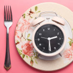 an alarm clock on an ornate, pink plate
