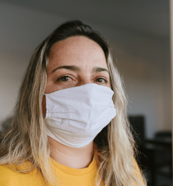 woman in a yellow sweater, wearing a mask during eating disorder treatment