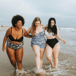 Three happy, curvy women at the beach.