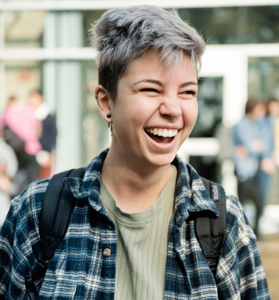 non binary individual smiling ad laughing outside