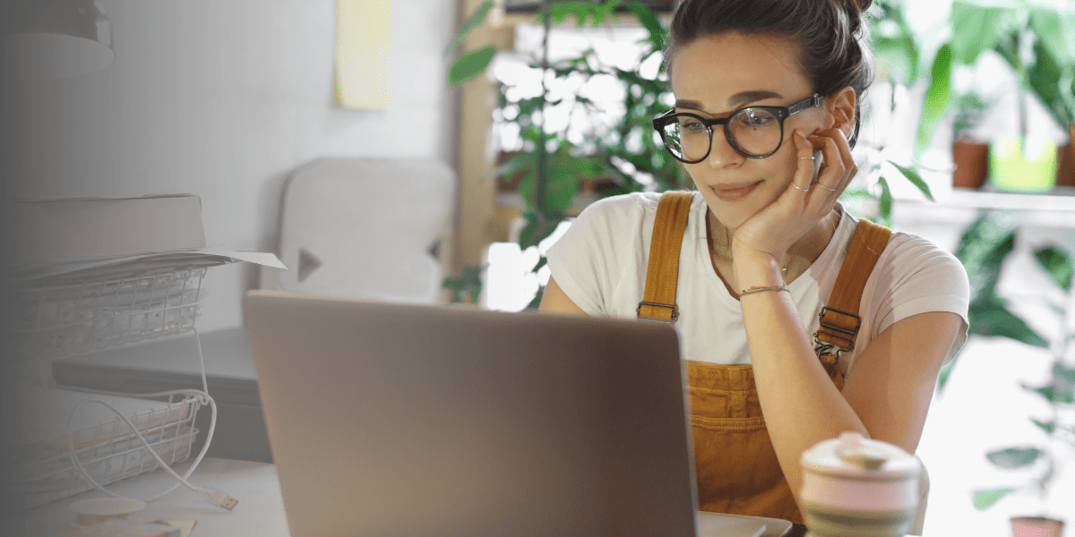 a young brunette woman wearing glasses rests her face in her hand as she looks at her laptop. Her living space is full of plants and soft light