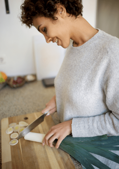 Virtual day treatment client smiles while meal prepping.