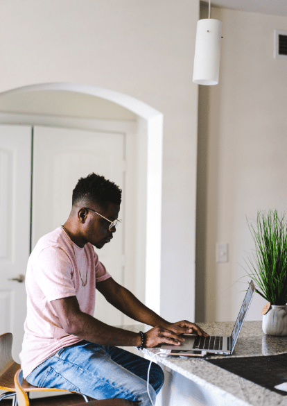 a young man wearing a pink shirt sits at his kitchen counter, participating in virtual day treatment