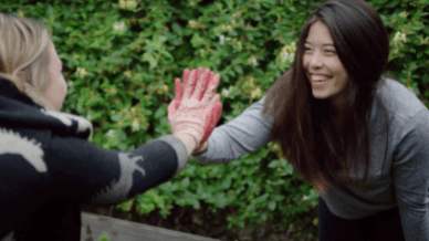 surrounded by greenery, two women high five, smiling and wearing gardening gloves