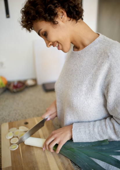 a young woman smiles as she chops leeks in her kitchen
